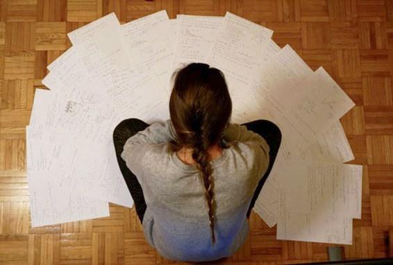 Immagine di ragazza che legge alcuni fogli sparsi sul pavimento